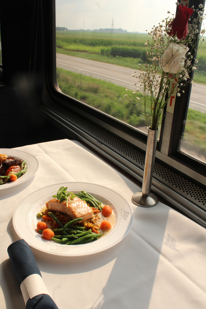 Plate of food on linen table cloth next to window of passenger car