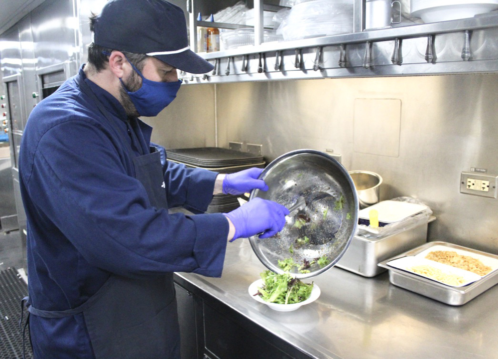 Man moving salad from mixing bowl to dish