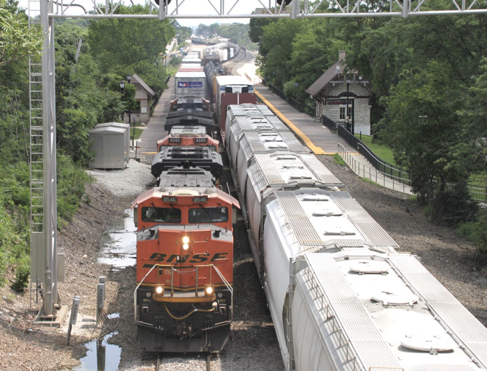 On three-track main, intermodal train on left-hand track catches up to freight train on center track.