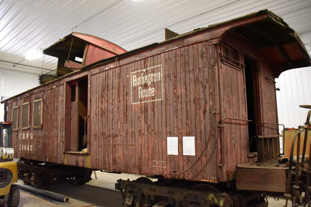 Faded red wooden caboose in restoration shop