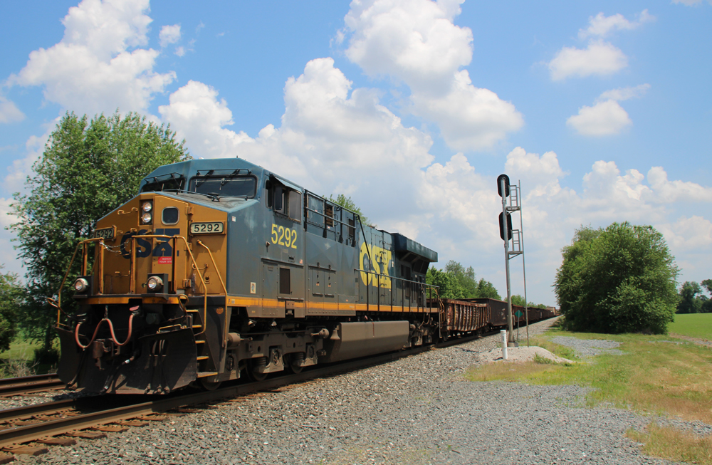 Train with one engine under blue sky with white clouds