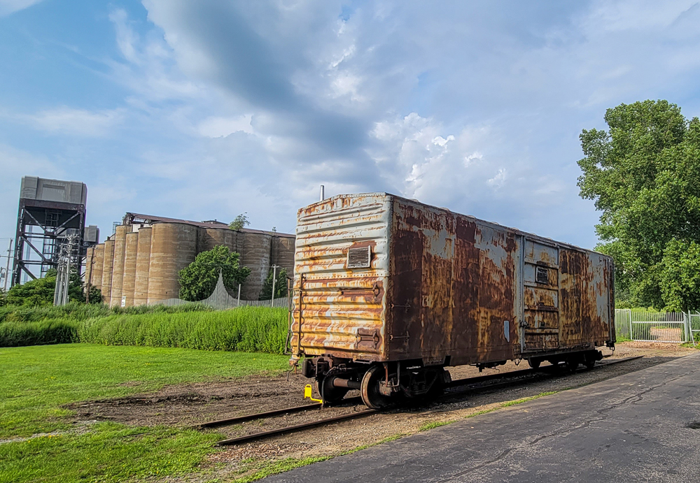 Rusted boxcar with grain silos in background