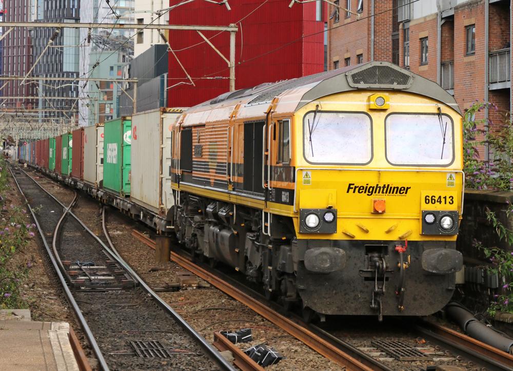 Yellow and orange locomotive pulling single-level contrainer train