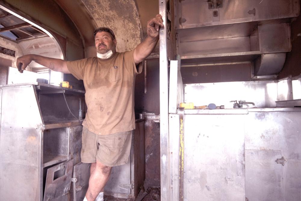 Workman in kitchen area of passenger car under restoration