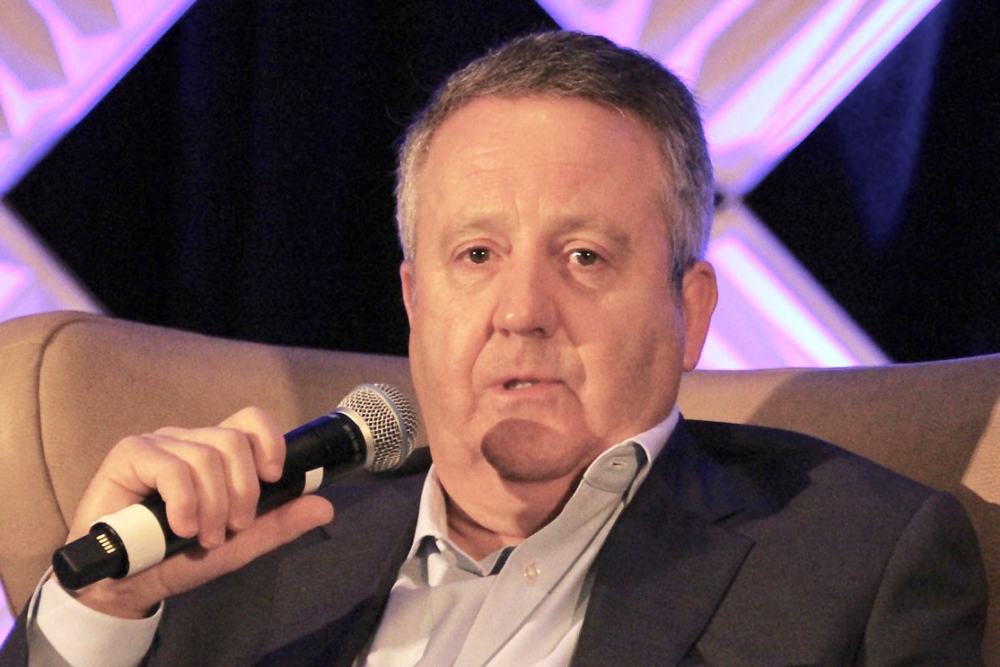 seated man in suit with microphone