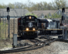 Black locomotive leads train through sharp curve