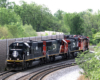 Long string of locomotives led by solid black engine passes through S curve