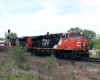 Two red and black locomotives with short passenger train passes signals