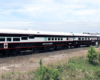 Black and white passenger cars with red trim — one with a glass back wall, one with a dome — pass on an inspection train.
