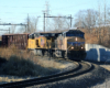 Two yellow diesels bring train downhill on sharp curve