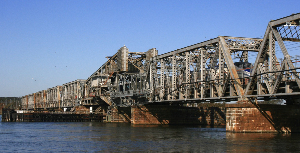 Long steel bridge with train barely visible through girders