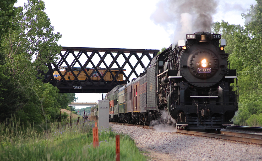 Passenger train with steam engine stops on straight as diesel crosses bridge in background