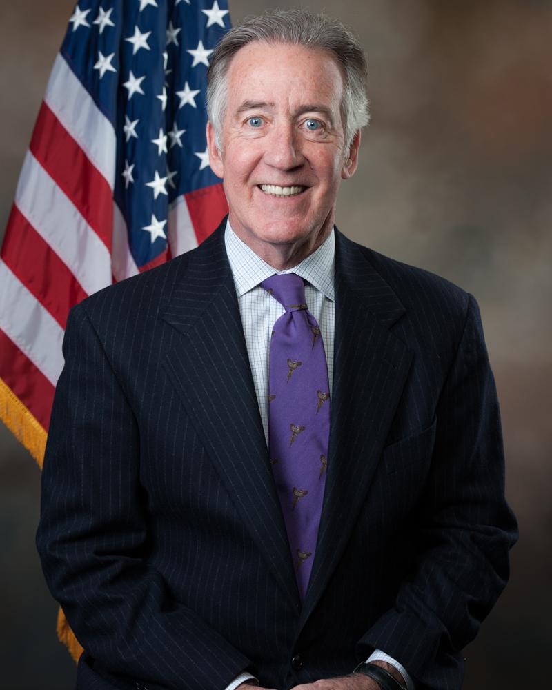 Congressman in dark suit in front of U.S. flag