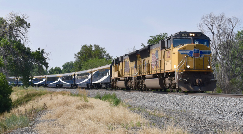 Two yellow locomotives leading blue, gold, and white passenger cars