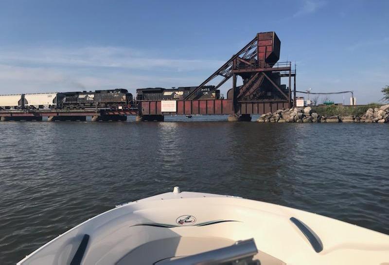 In view from small boat, train crosses bridge