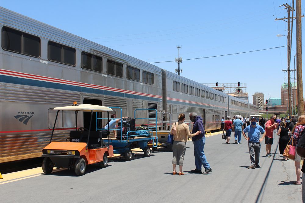Passenger cars at station with baggage being unloaded onto trailer and passengers walking on platform