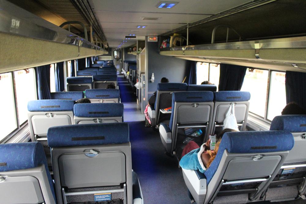 Interior of passenger car looking forward along aisle between coach seats