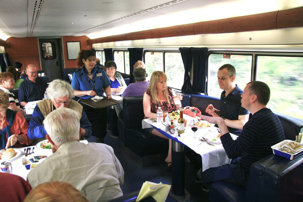 Dining tables of passenger car filled with passengers