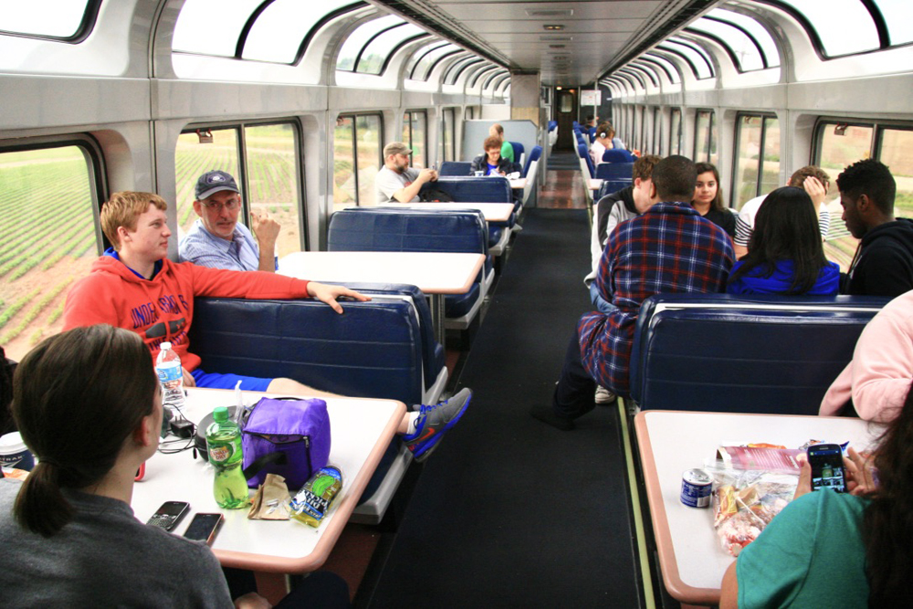 Passengers enjoying view while seated at tables in lounge car