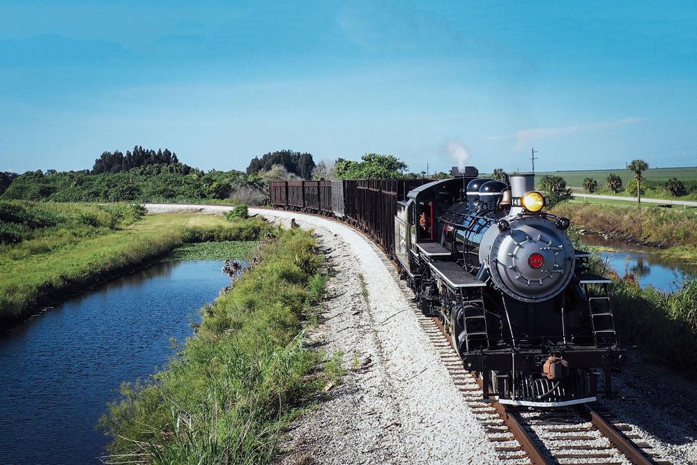 Steam locomotive leads train on curve