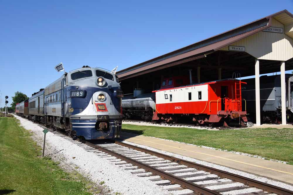 Blue-and-gray diesel locomotive pulls train along fence line.