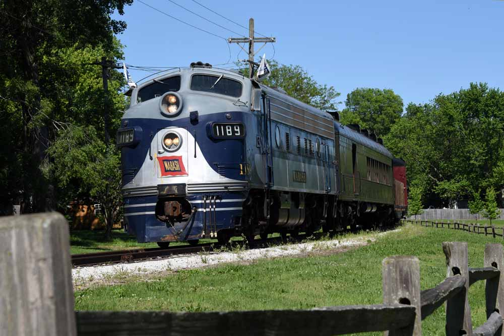Blue-and-gray diesel locomotive pulls train along fence line