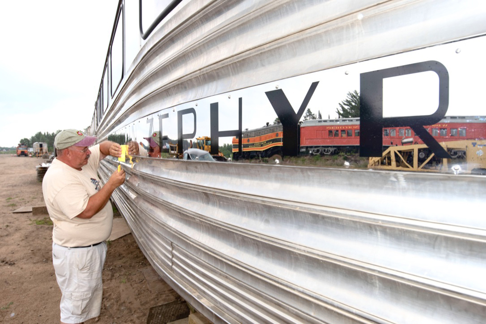 Man works on side of stainless steel passenger car