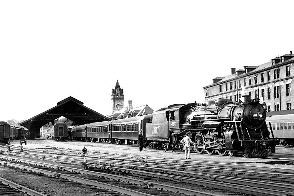 Steam-powered passenger train pull out of train shed