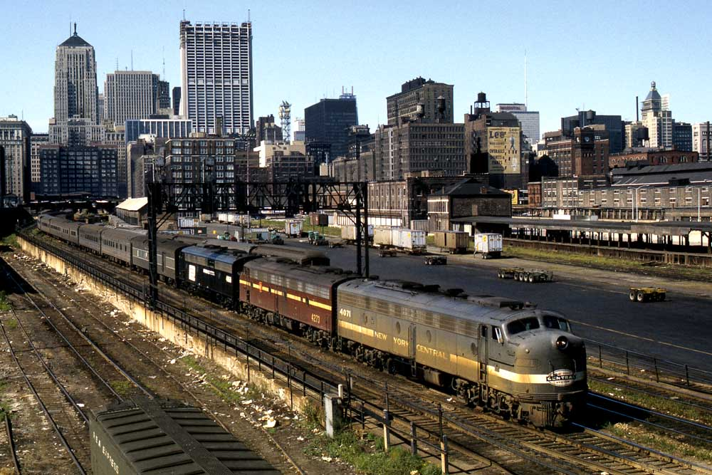 Multi-colored diesels move passenger train under signal bridge and out of downtown landscape