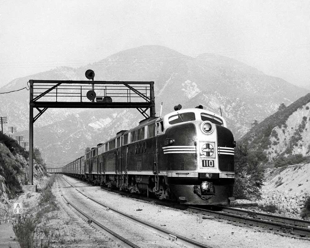 Diesel locomotive set leads a freight train through hills and under a signal bridge