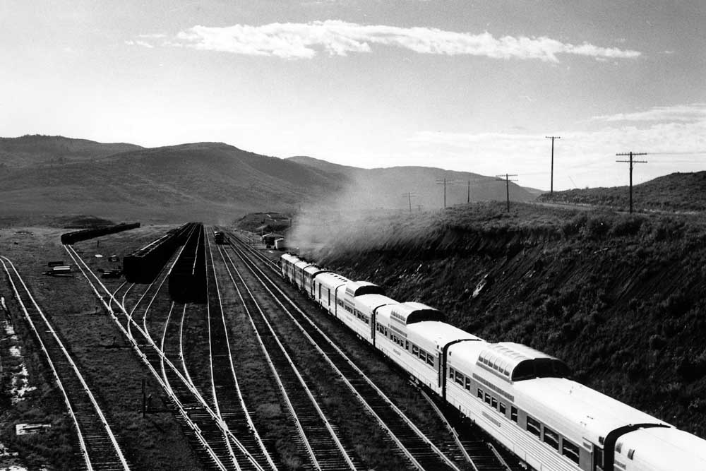 Streamlined passenger train rolls into valley alongside yard tracks filled with hoppers