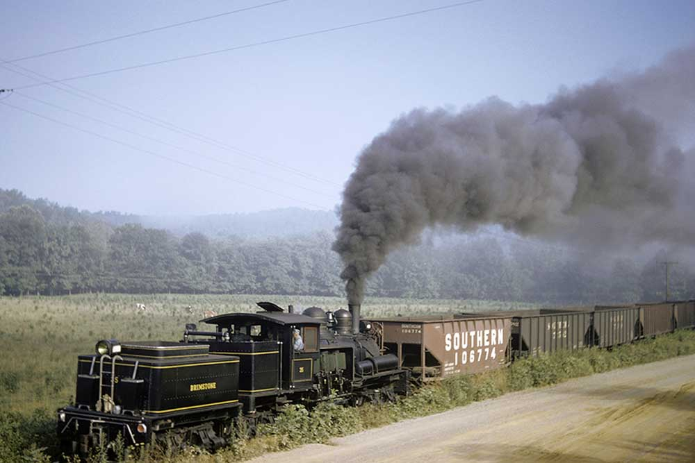 Geared steam locomotive reverses with coal cars