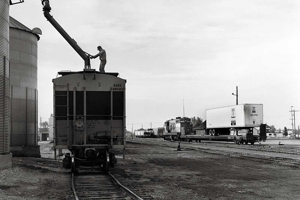 A man guides loading chute into covered hopper while short freight train passes