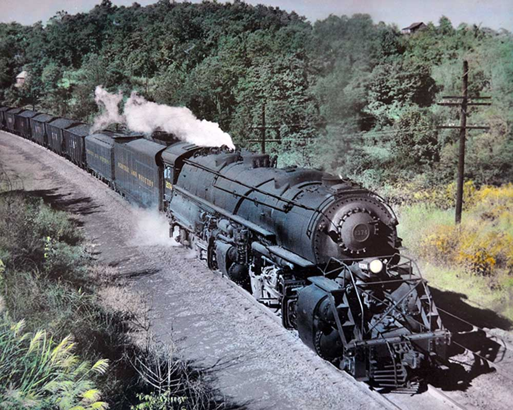 Large smoking steam locomotive climbs upgrade with train on curve