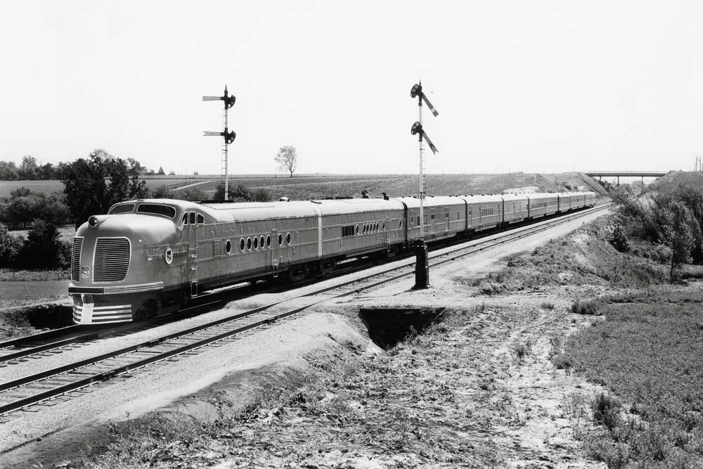 Streamlined passenger train split semaphore-type signals with overpass in distance