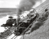 Black-and-white overhead view of steam locomotive with freight train beside ocean