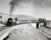 Black-and-white view of steam locomotive with freight train crossing bridge over another railroad and a highway.