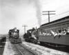 Black-and-white view of two steam locomotives meeting, with sailors looking out from coach