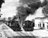 Black-and-white view of steam locomotives heading two narrow-gauge trains on lines converging in a small town