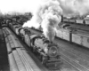 Black-and-white overhead view of steam locomotive with freight train in freight yard