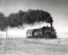 Black-and-white view of 4-6-0 steam locomotive making smoke with 1-car train in desert
