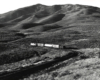 Black-and-white view of road-switcher diesel locomotive with short freight train amid barren hills