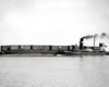 Black-and-white broadside view of tugboat with barge carrying freight cars