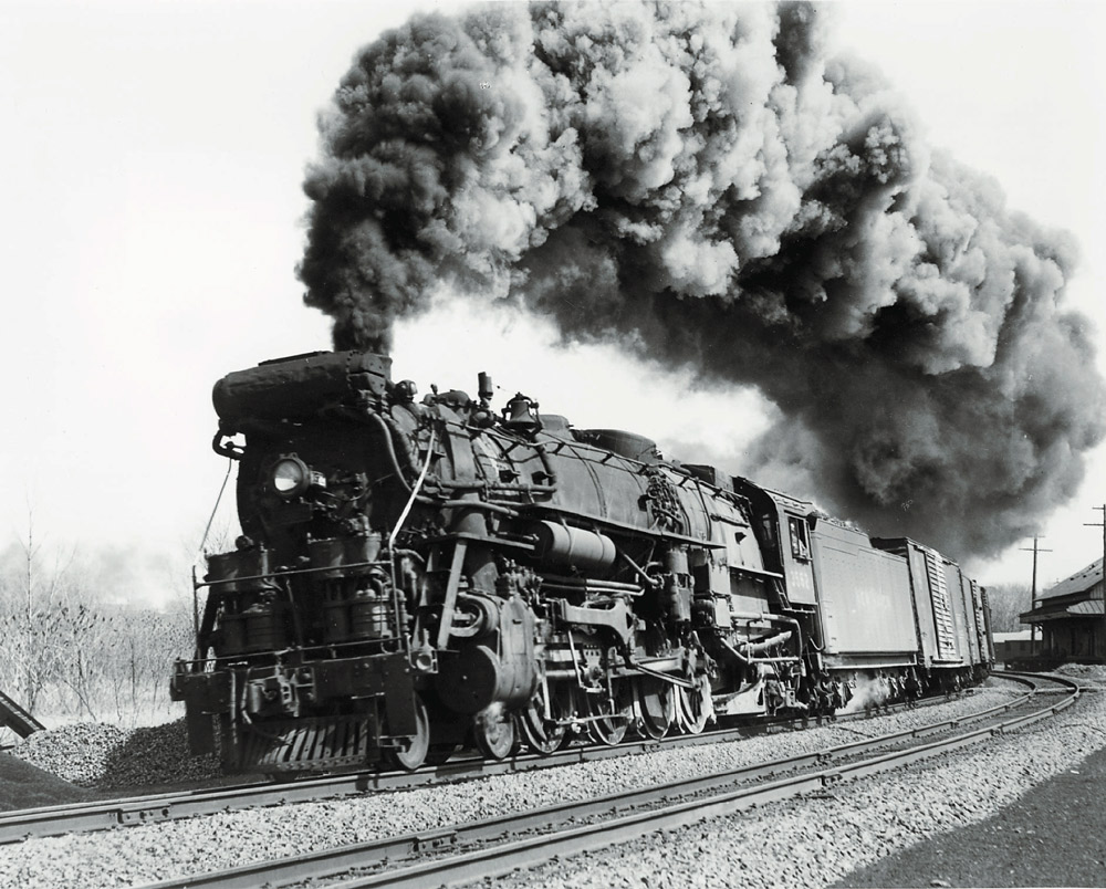 Low-angle black-and-white photo of 4-8-2 steam locomotive making smoke with freight train