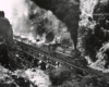 Black-and-white overhead view of 2-6-6-2 steam locomotive with freight train crossing bridge in mountains