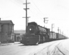 Black-and-white view of steam locomotive with freight train on track in a city street