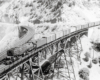 Black-and-white overhead view of steam locomotive with freight train on trestle in mountains