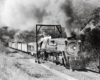 Black-and-white view of steam locomotive with freight train in mountains