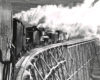 Black-and-white view from behind of two steam locomotives pushing a rotary snowplow on a trestle