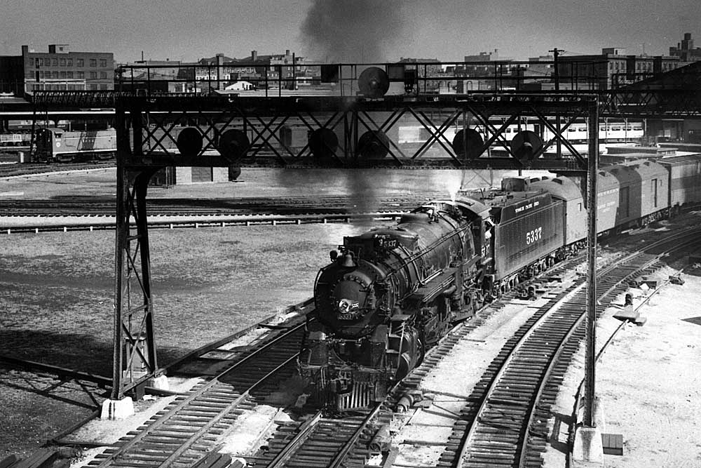 Steam locomotive with passenger train paused underneath a signal bridge in a black and white image.